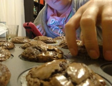 girl reaching for brownie muffin
